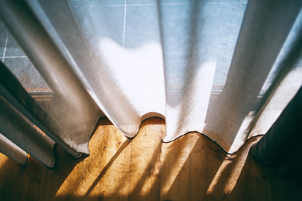 A photograph of a curtain hanging across a window, it touches a wooden floor