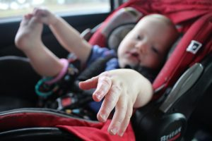 A photograph of a baby inside a car-seat