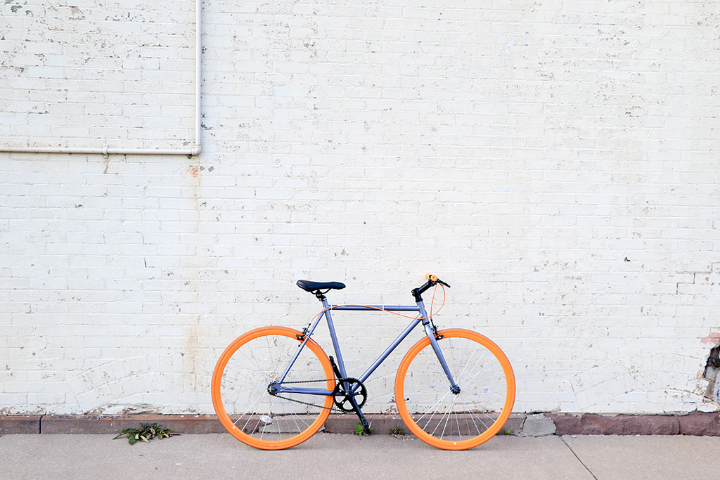 A photograph of a blue and orange bicycle against a white brick wall