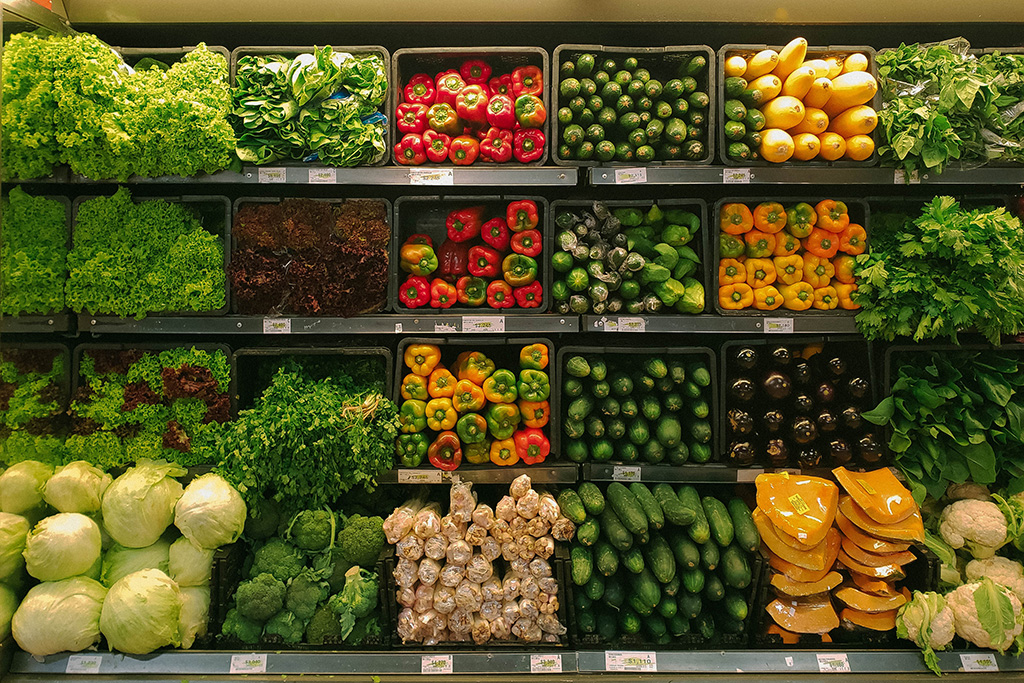 A photograph of a supermarket shelf, filled with loose vegetables