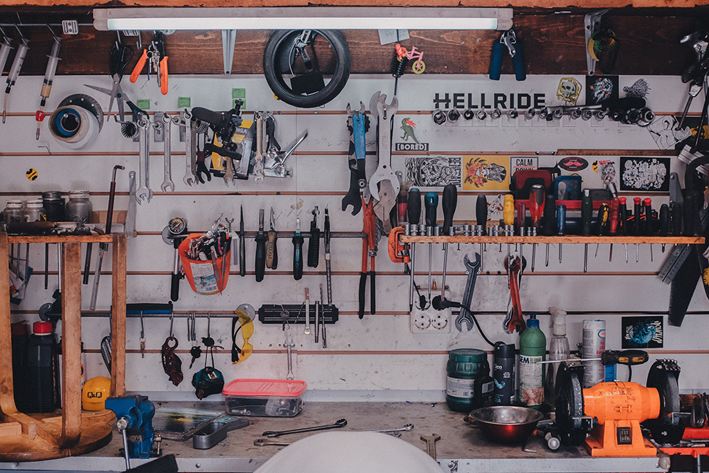 An image of a workshop, filled with tools hanging on the wall and sitting on the bench